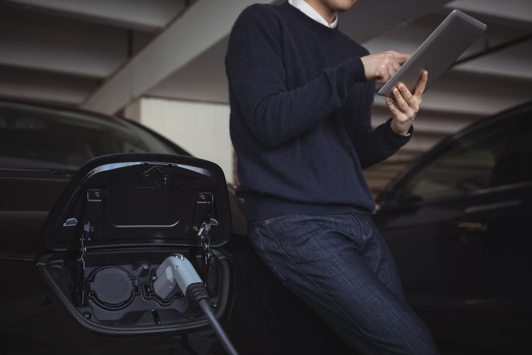 Man using digital tablet while charging electric car in garage Free Stock Images from PikWizard