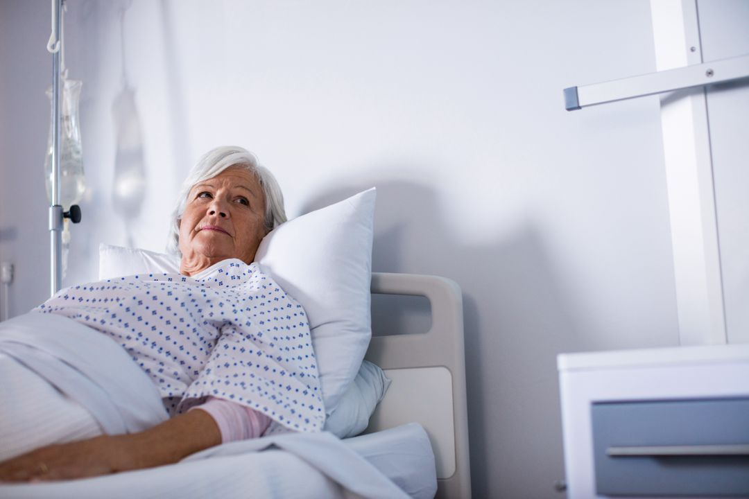Thoughtful senior woman lying on bed in hospital Free Stock Images from PikWizard