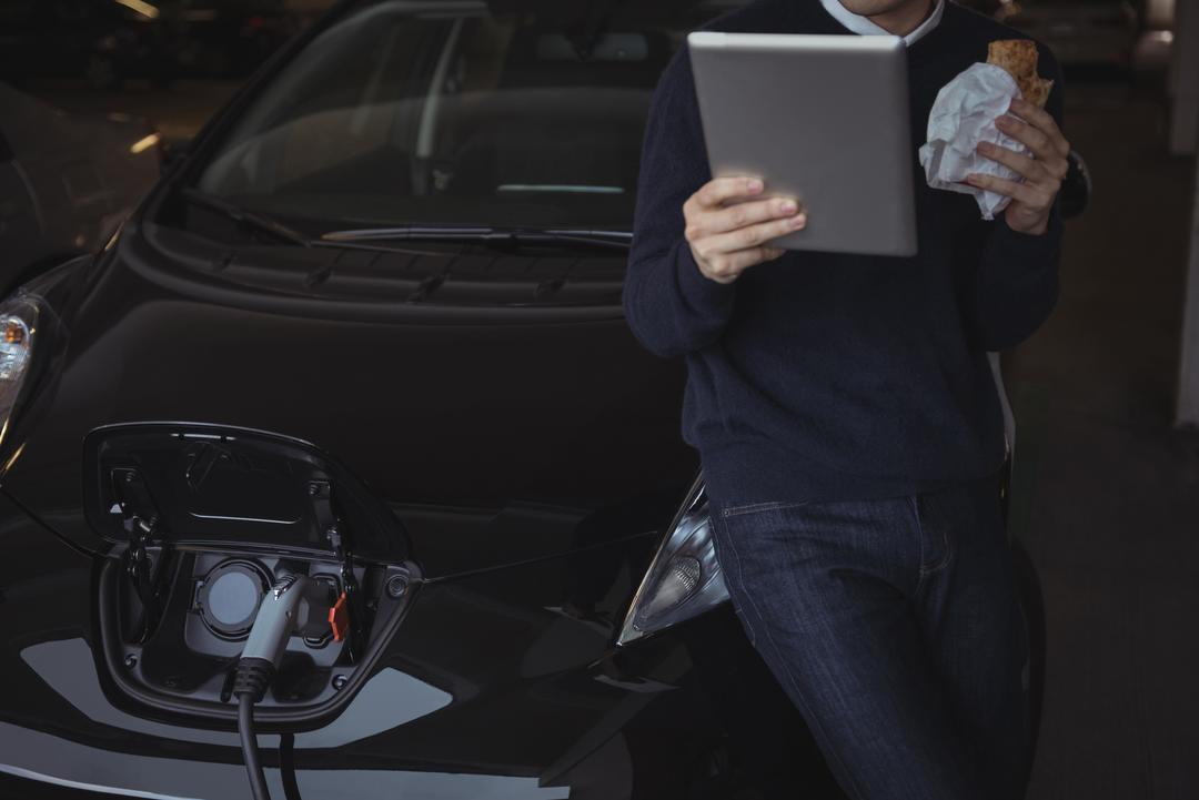 Man using digital tablet while charging electric car in garage