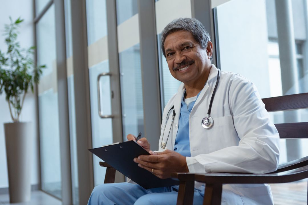 Side view of mature male doctor writing on clipboard while sitting on chair in lobby at hospital Free Stock Images from PikWizard