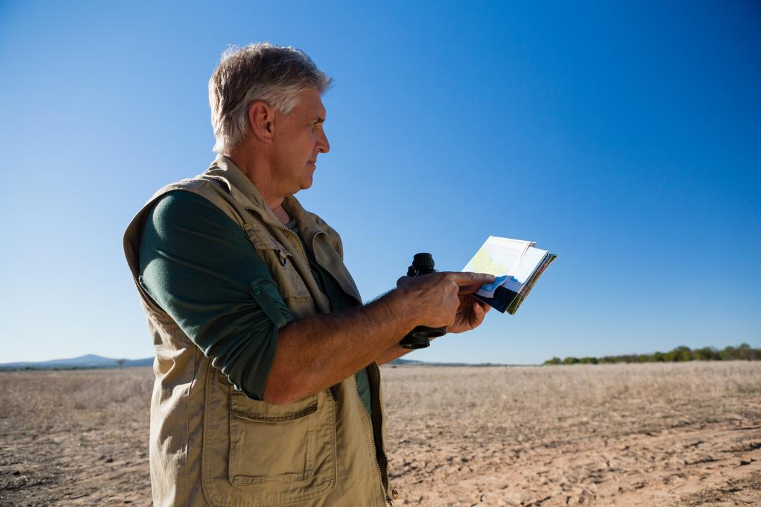Man holding map and binocular against blue sky on landscape Free Stock Images from PikWizard