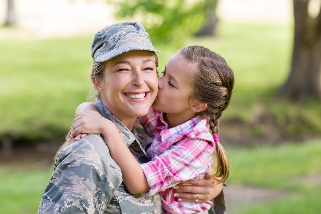 Happy female soldier being kissed by her daughter in park on sunny day