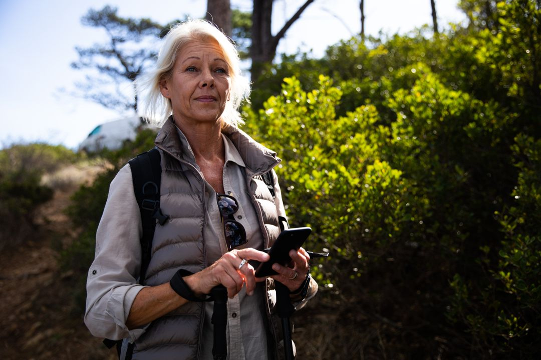 Front view portrait of a senior Caucasian woman enjoying her time in nature, walking in the woods, using a smartphone