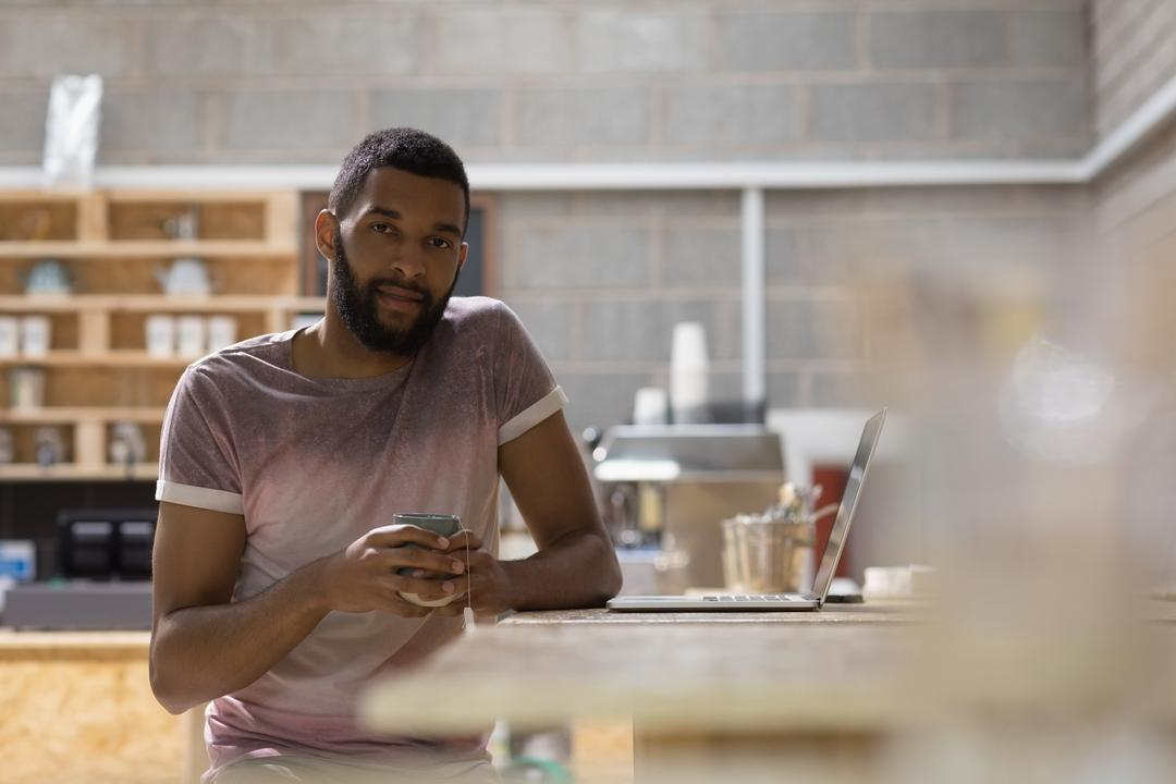 Portrait of young man holding coffee cup while sitting with laptop at table in cafe