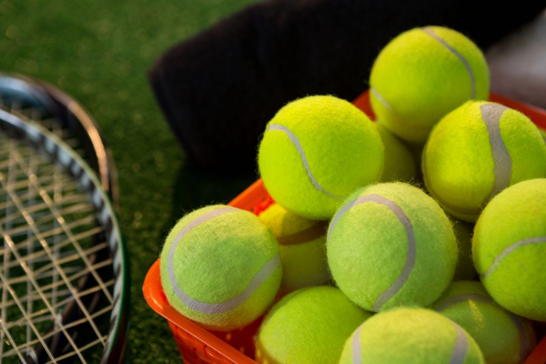 Close up of tennis balls in basket by rackets on field  Free Stock Images from PikWizard
