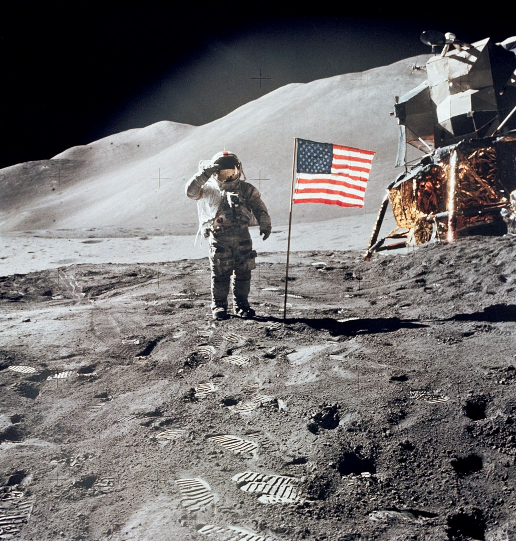 "AS15-88-11863 (1 Aug. 1971) --- Astronaut David R. Scott, commander, gives a military salute while standing beside the deployed United States flag during the Apollo 15 lunar surface extravehicular activity (EVA) at the Hadley-Apennine landing site. The flag was deployed toward the end of EVA-2. The Lunar Module (LM), ""Falcon,"" is partially visible on the right. Hadley Delta in the background rises approximately 4,000 meters (about 13,124 feet) above the plain. The base of the mountain is approximately 5 kilometers (about three statue miles) away. This photograph was taken by astronaut James B. Irwin, lunar module pilot. While astronauts Scott and Irwin descended in the LM to explore the moon, astronaut Alfred M. Worden, command module pilot, remained in lunar orbit in the Command and Service Modules (CSM)."