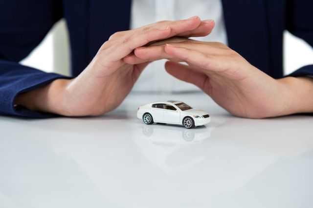 Businesswoman protecting toy car with hands