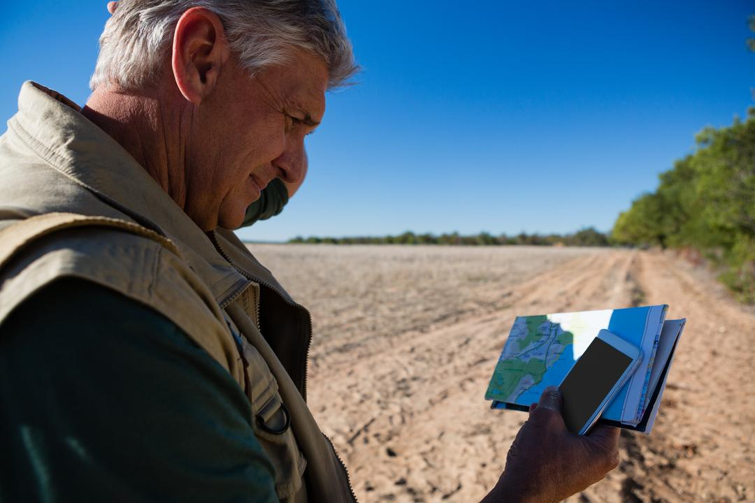 Man with map using mobile phone on landscape