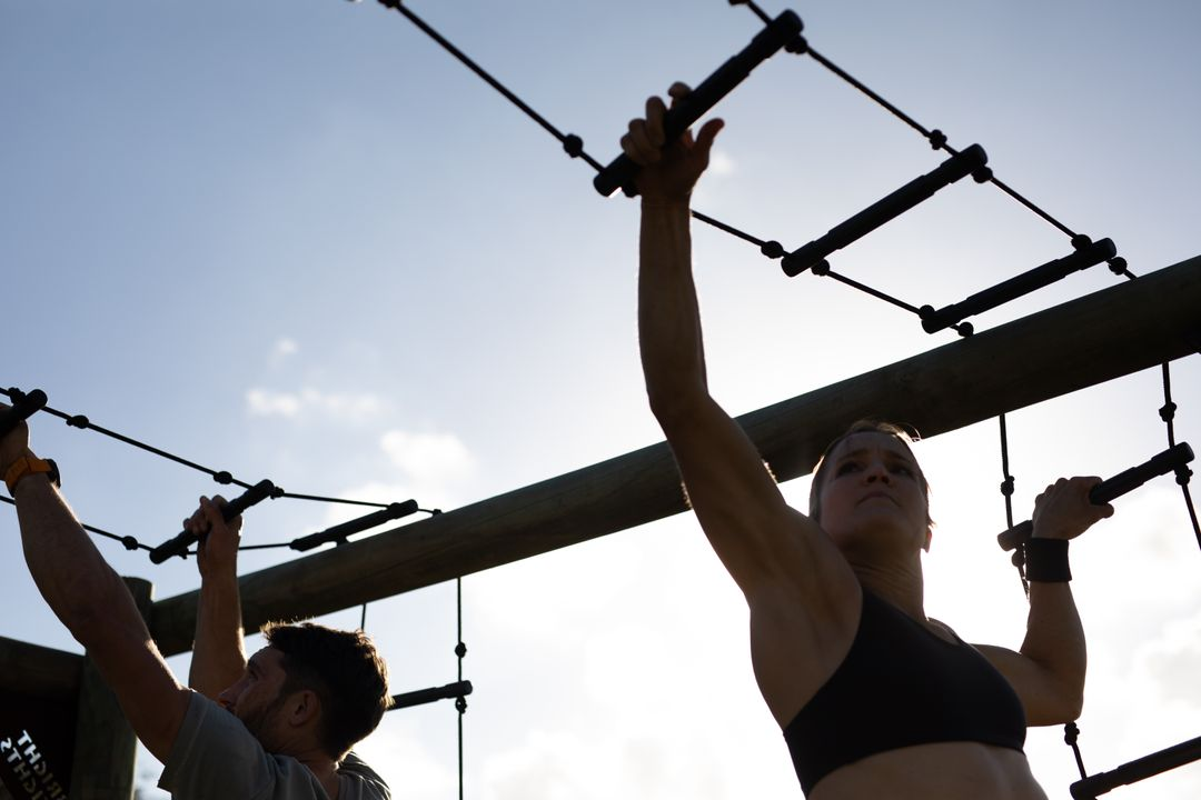 Low angle view of a Caucasian woman and man wearing sports clothes hanging from rope ladder monkey bars on a climbing frame at an outdoor gym during a bootcamp training session Free Stock Images from PikWizard