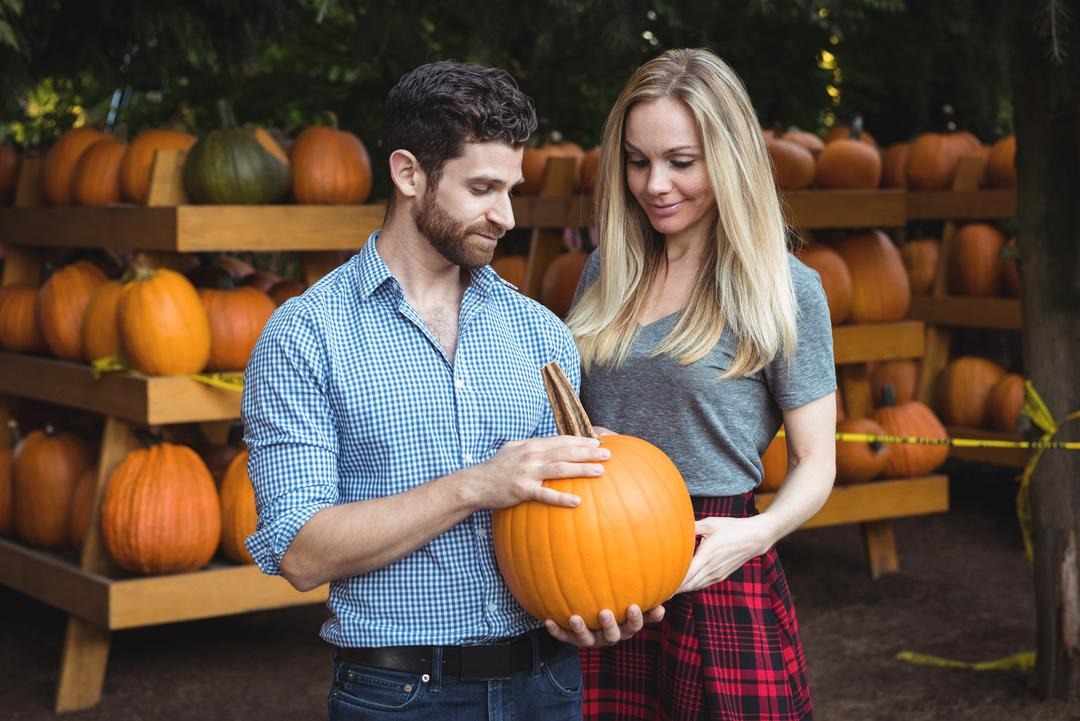 Couple holding pumpkin in supermarket