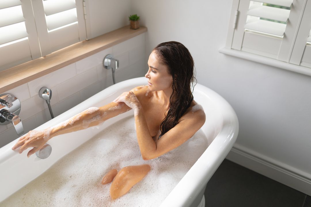 Beautiful woman taking bubble bath in bathroom at home Free Stock Images from PikWizard