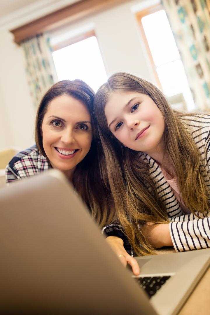 Portrait of mother and daughter using laptop in living room at home
