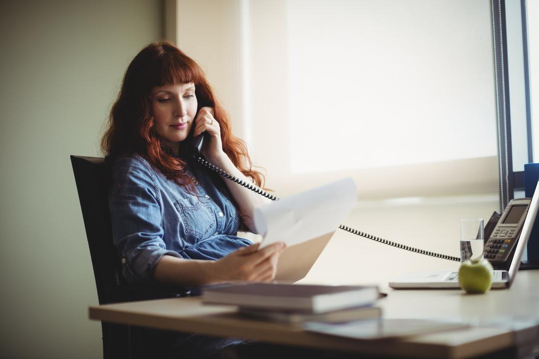 Pregnant businesswoman talking on telephone while working in office Free Stock Images from PikWizard