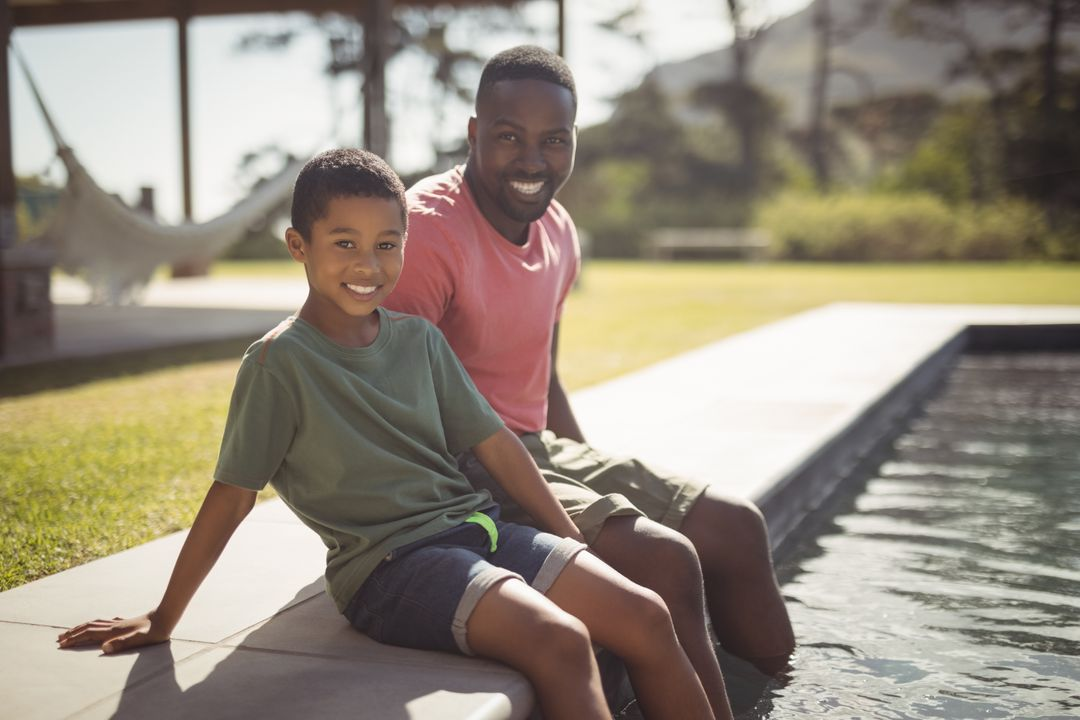 Portrait of smiling father and son sitting on edge of swimming pool