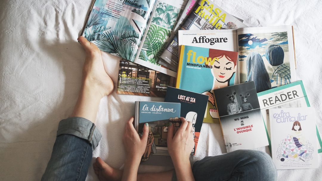 Woman sitting on a bed surrounded with print magazines ads