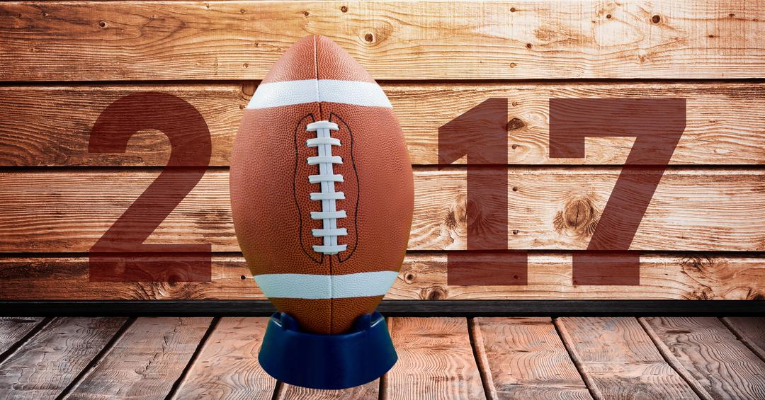 Digital composition of 2017 new year message with football against wooden background