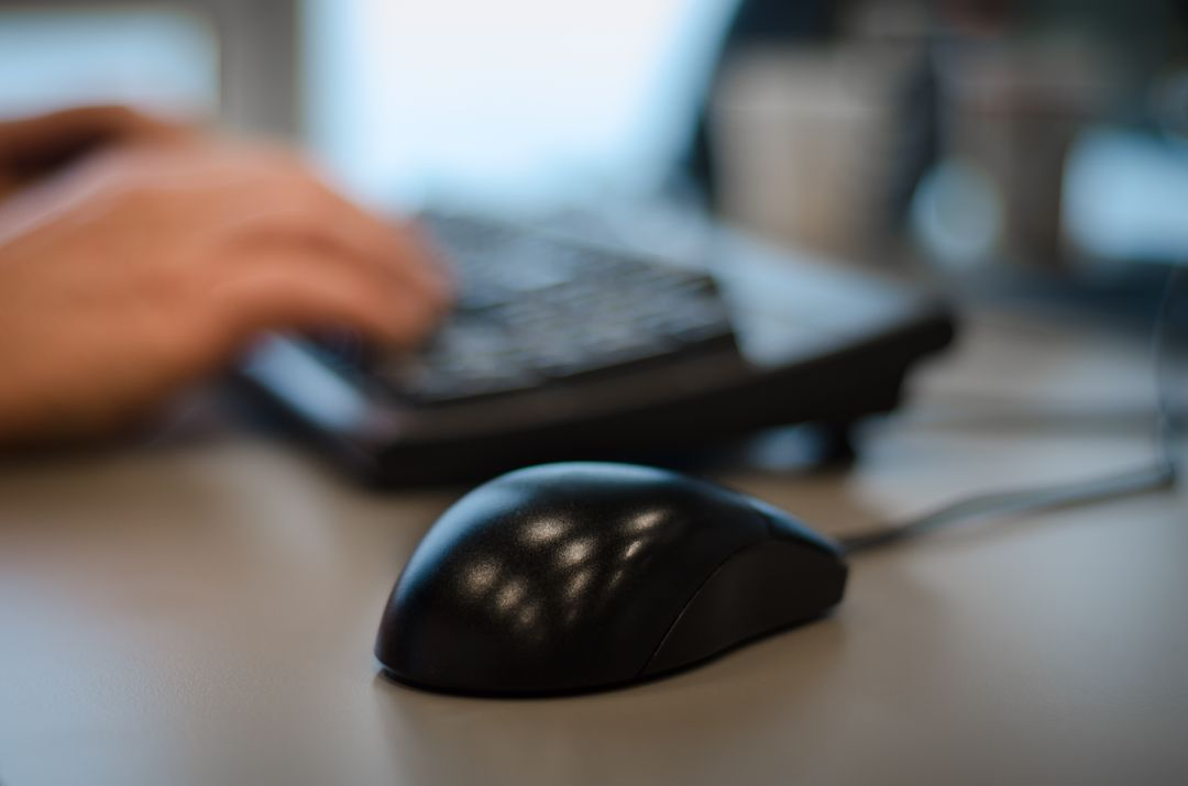 closeup of a computer mouse in foreground with a person. typing in the background