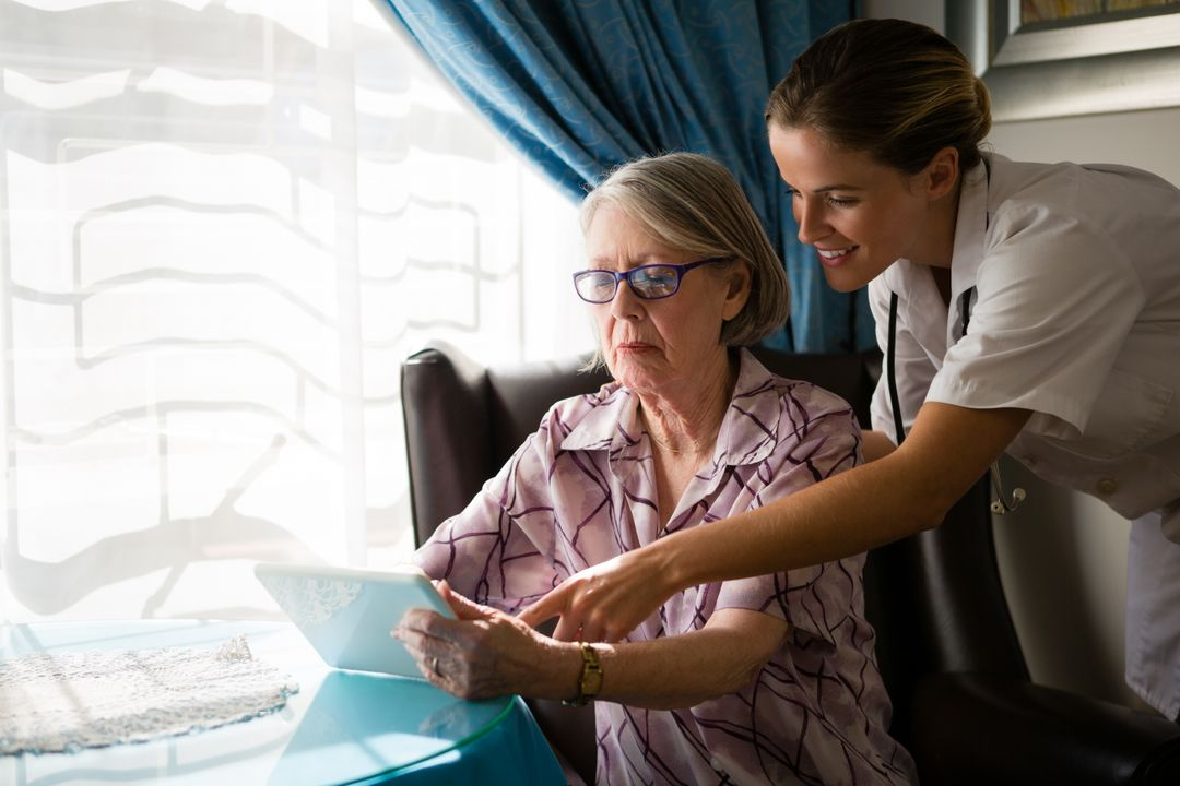 Female doctor assisting woman in using digital tablet at nursing home Free Stock Images from PikWizard