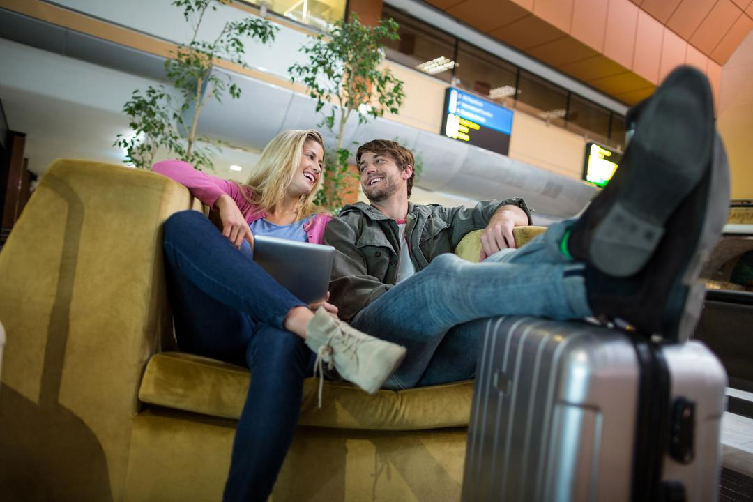 Smiling couple interacting with each other in waiting area at airport terminal Free Stock Images from PikWizard