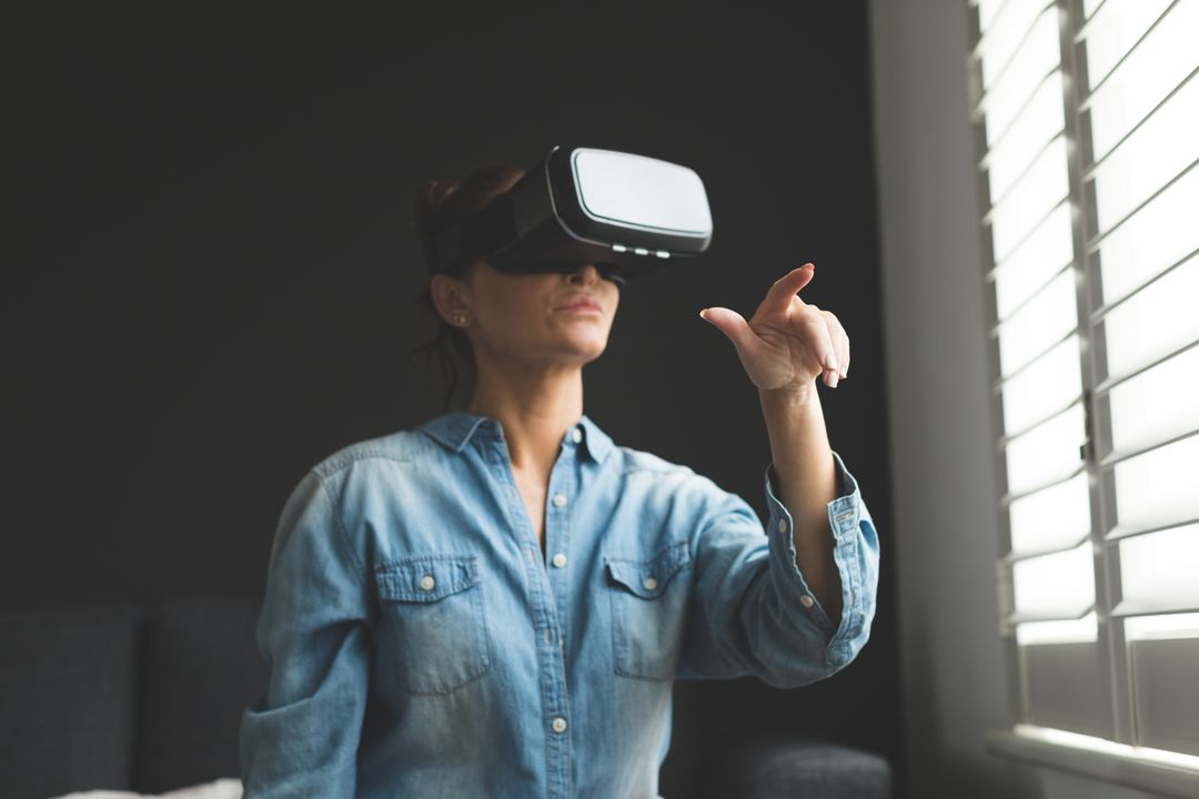 Beautiful woman using virtual reality headset while sitting on sofa in a comfortable home