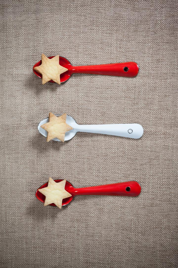 Red and white spoon with christmas cookies arranged on tablecloth