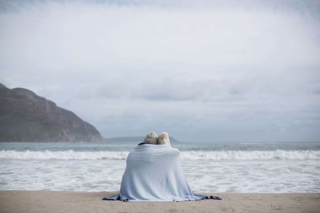 Rear view of mature couple wrapped in blanket on the beach Free Stock Images from PikWizard