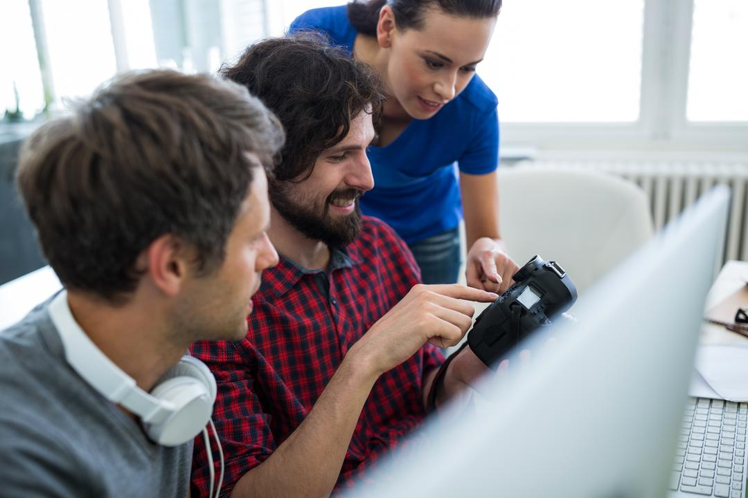 Male graphic designers showing pictures to his coworkers on camera in office