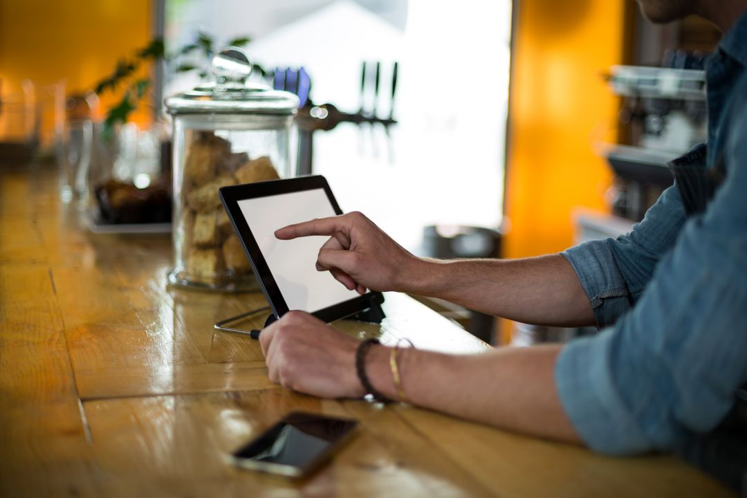 Waiter standing at counter using digital tablet in café Free Stock Images from PikWizard
