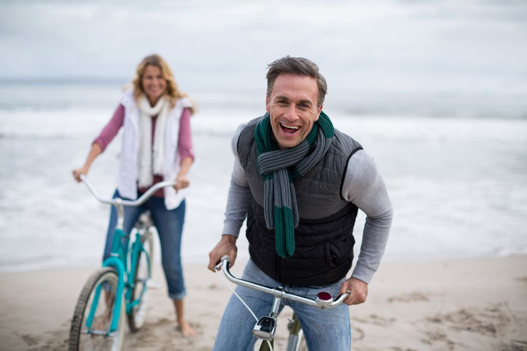 Portrait of mature couple riding bicycles on the beach