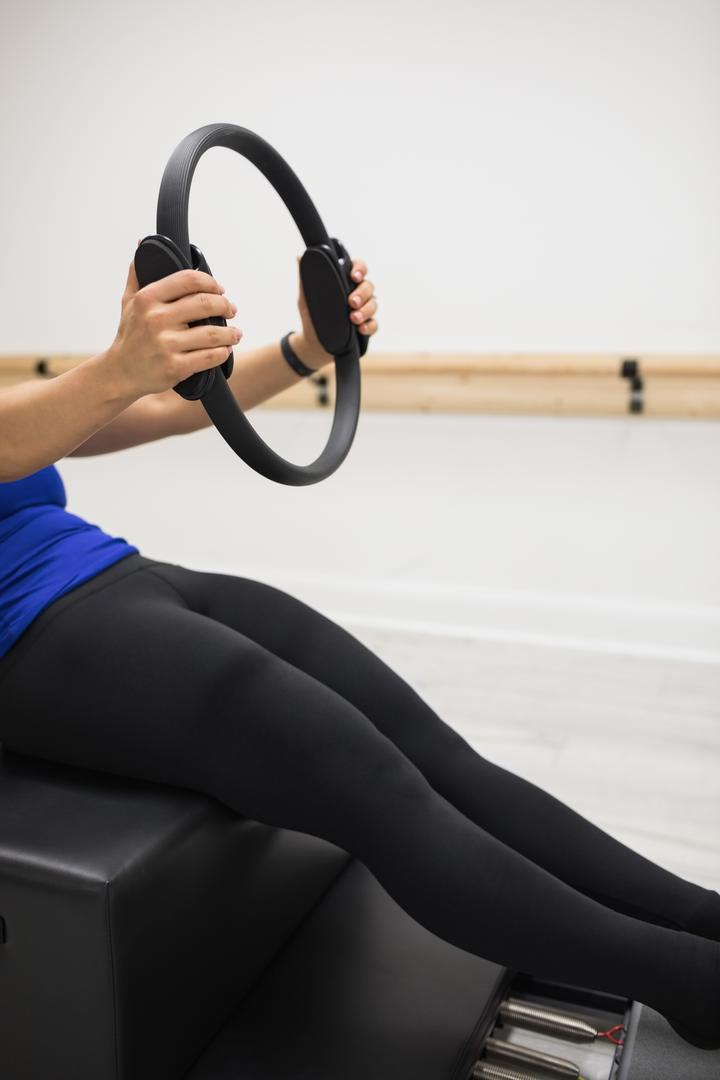 Mid section of woman exercising with pilates ring in gym