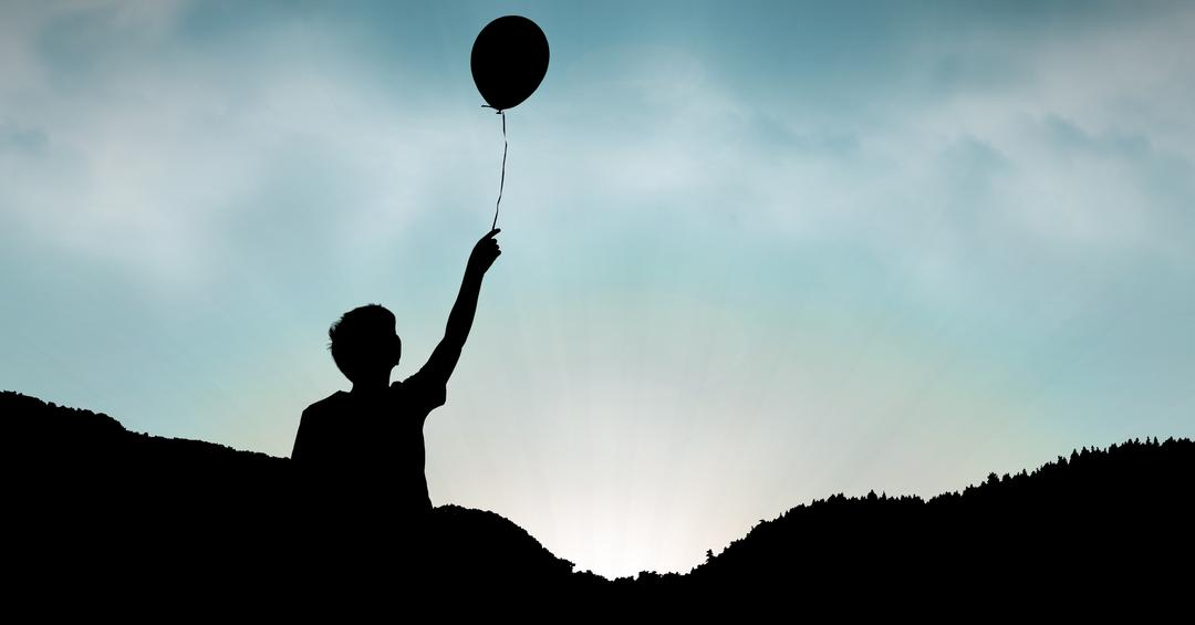 Digital composite of Silhouette boy holding balloon against sky during sunset Free Stock Images from PikWizard