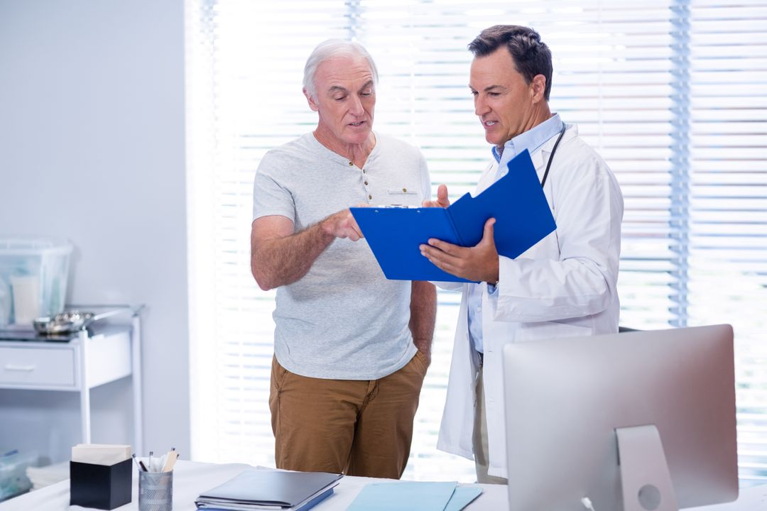 Doctor and senior man discussing on file in clinic Free Stock Images from PikWizard