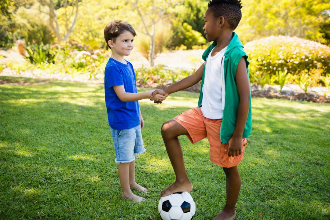 Cute football players handshaking  on a park