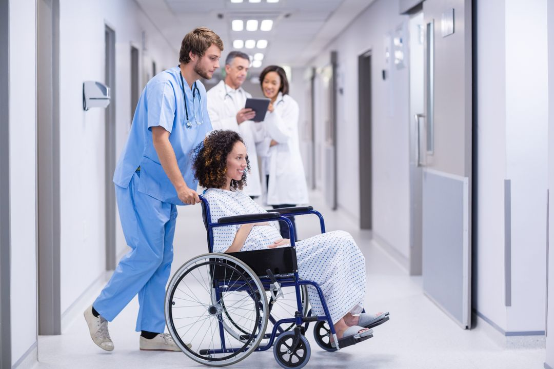 Doctor pushing a pregnant woman on wheelchair in hospital Free Stock Images from PikWizard