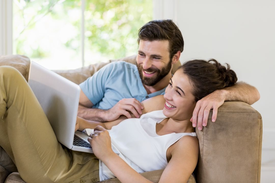 Happy couple lying on sofa and using laptop at home Free Stock Images from PikWizard