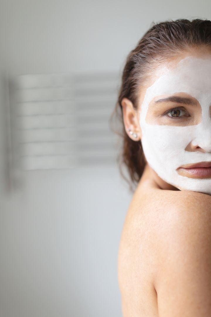 Portrait of woman with facial mask standing in bathroom at home