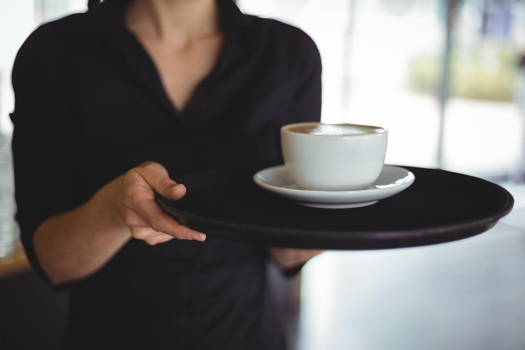 Mid section of waitress standing with cup of coffee in cafe