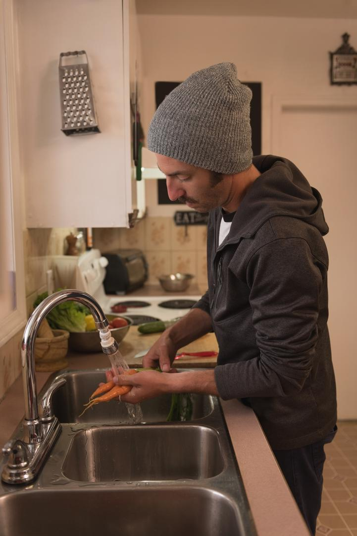 Man washing carrots in kitchen at home