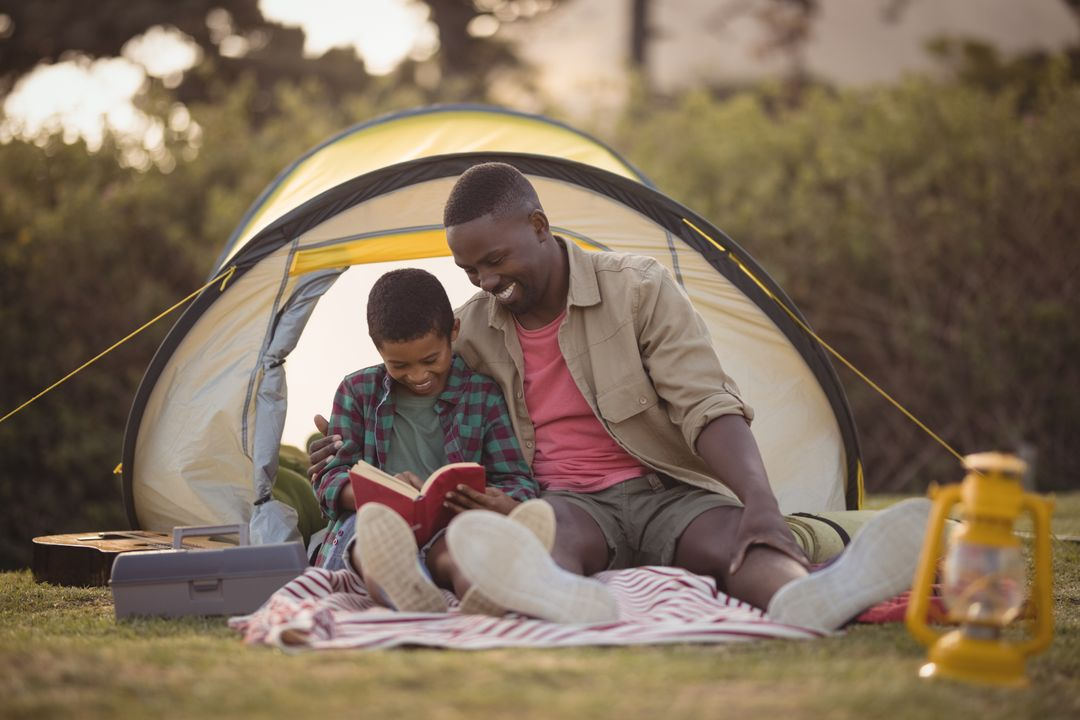 Father and son sitting in tent reading a book