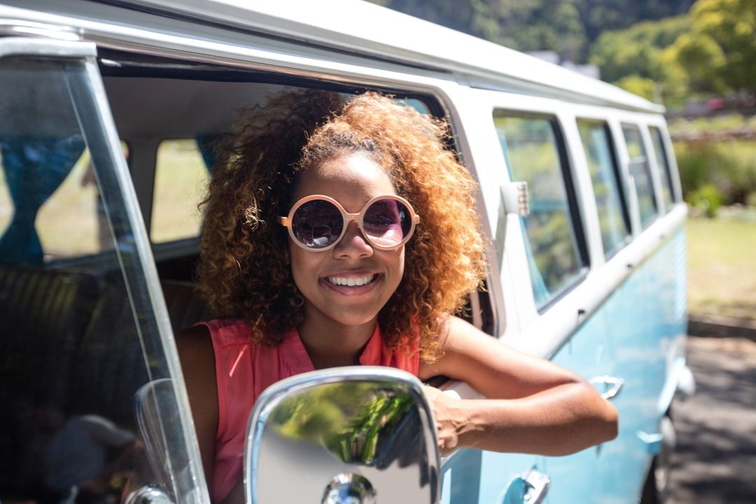 Smiling woman looking out of camper van window on a sunny day Free Stock Images from PikWizard