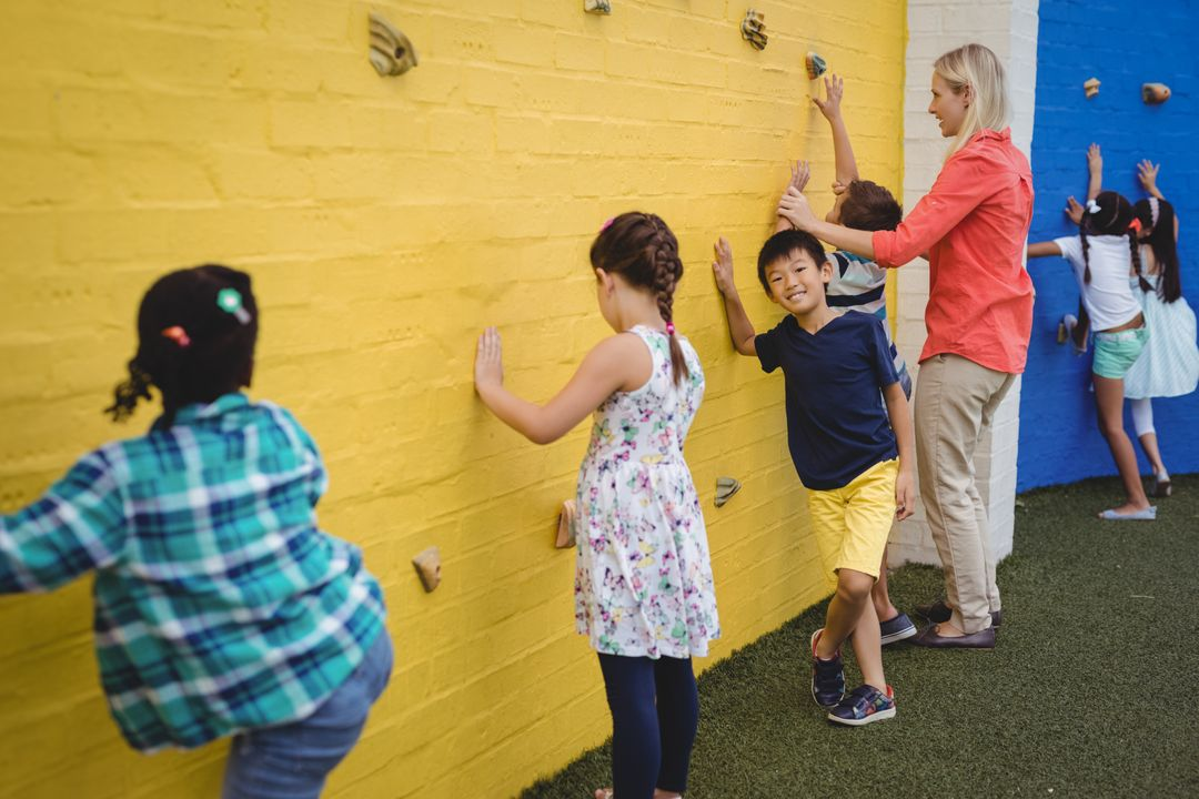 Trainer assisting kids in climbing wall in school Free Stock Images from PikWizard