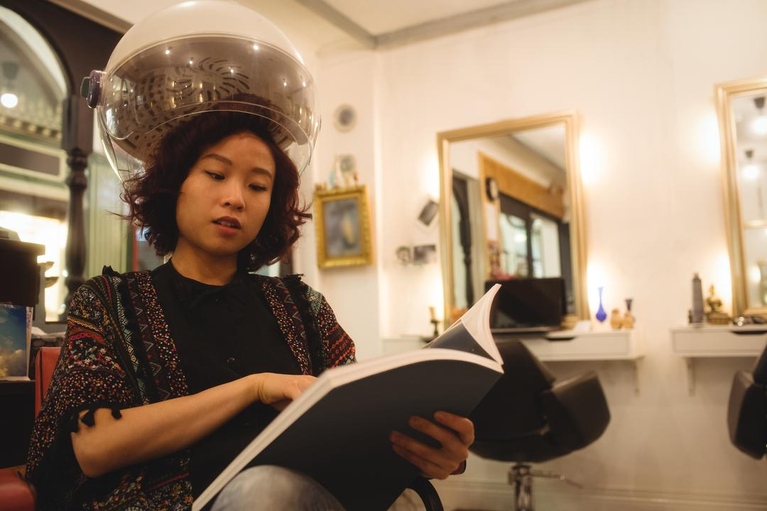 Stylish woman reading a magazine while sitting under a hairdryer at hair salon