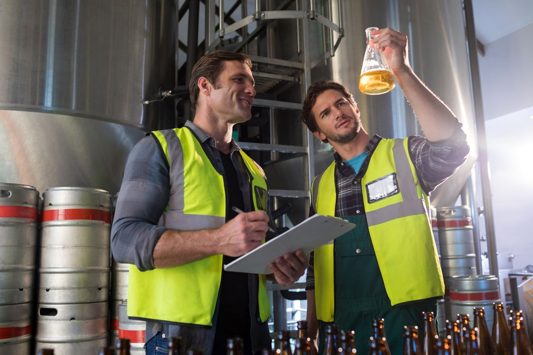 Coworkers examining beer in beaker at warehouse Free Stock Images from PikWizard
