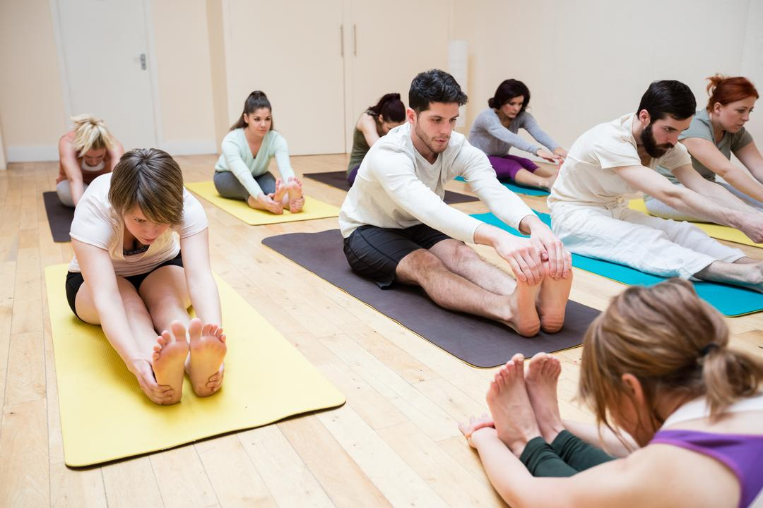 Trainer assisting group of people with pashimottanasana exercise in fitness studio