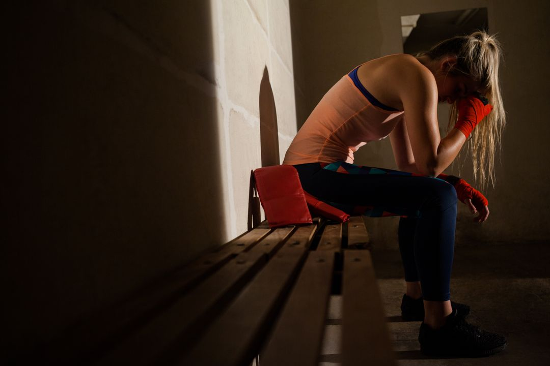 Sad woman sitting on bench in fitness studio Free Stock Images from PikWizard