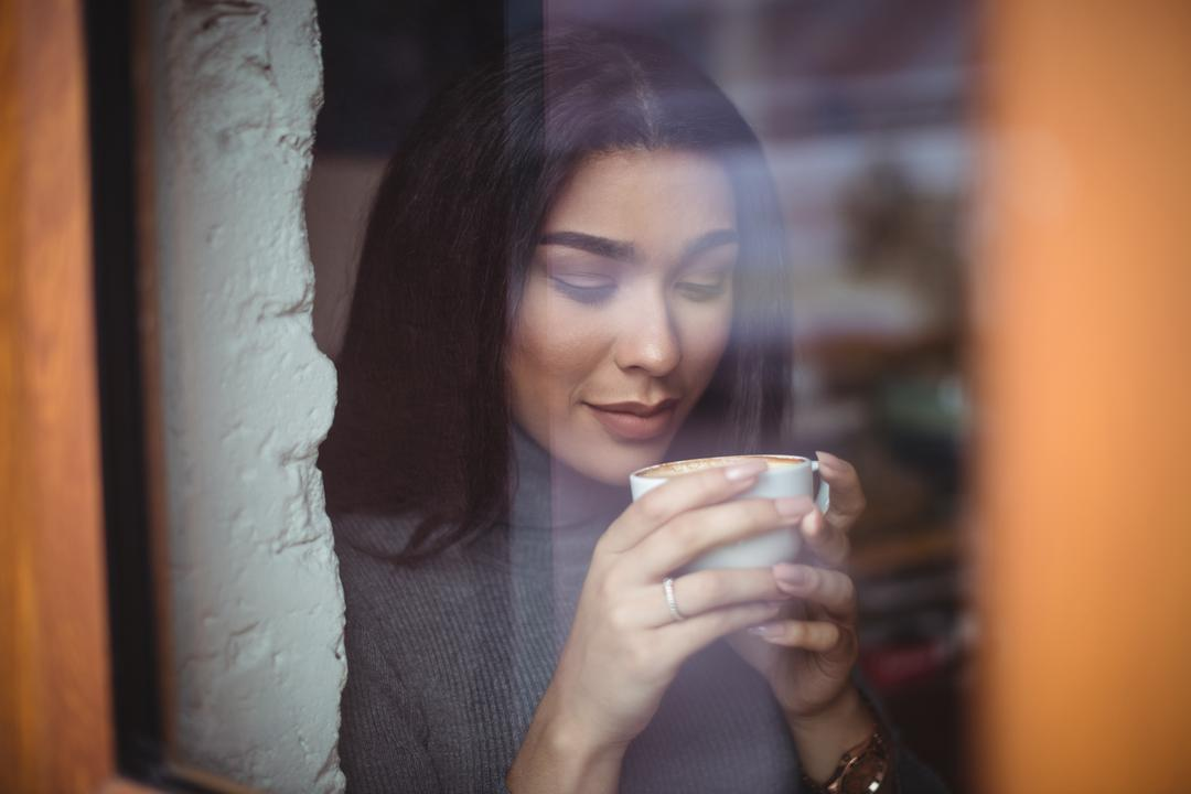Beautiful woman having a cup of coffee in café