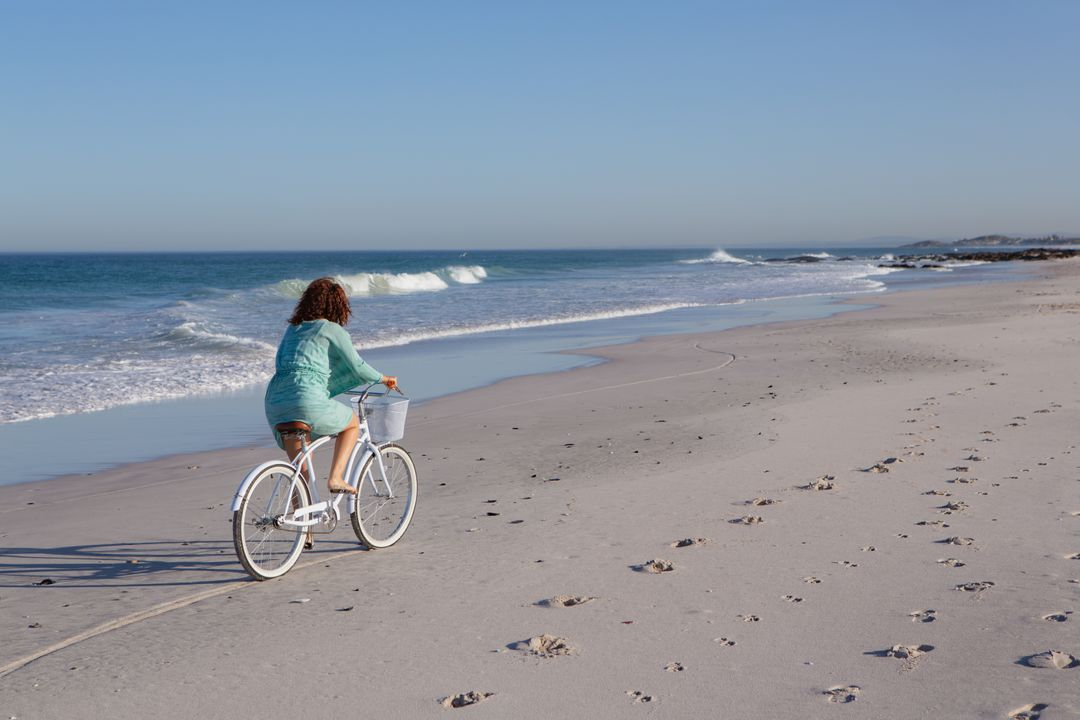 Rear view of woman riding bicycle on beach in the sunshine