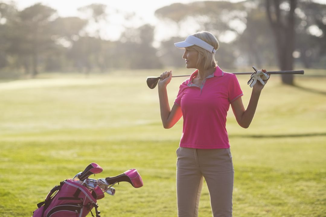 Confident mature woman carrying golf club while standing on field Free Stock Images from PikWizard