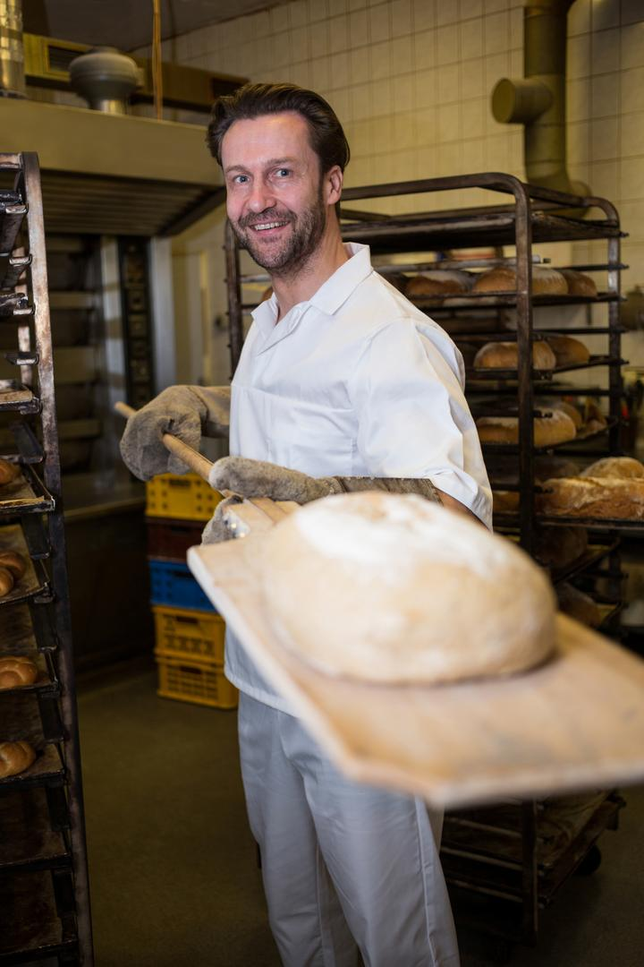 Smiling baker holding the baked bun in wooden spoon