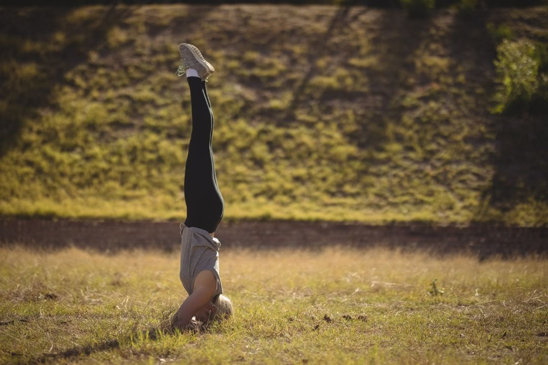 Woman performing headstand during obstacle course in boot camp Free Stock Images from PikWizard
